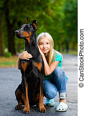 blonde girl hugs her beloved dog or doberman in summer park