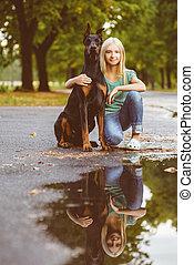 blonde girl hugs her beloved dog or doberman in summer park. Warm toned image