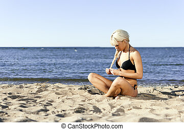 blonde girl in a black bathing suit sitting on shore blue sea