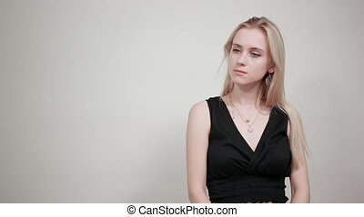 blonde girl in a black dress over isolated white background shows emotions