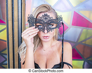 Blonde girl in a black masquerade mask.