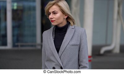 Blonde girl in a gray coat goes against the background of a modern glass building