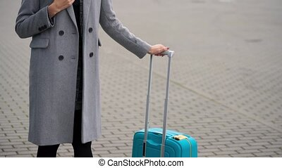 Blonde girl in a gray coat with a suitcase stands near the airport terminal