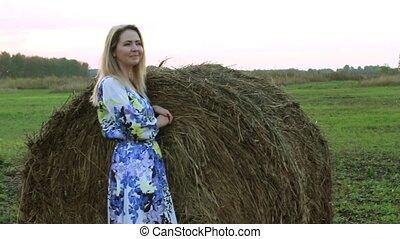 Blonde girl in a long dress near the straw sheaves