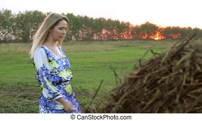 Blonde girl in a long dress near the straw sheaves