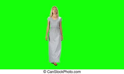 Blonde girl in a long grey dress going and looking straight into the camera against a green screen