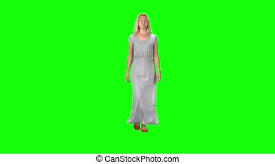 Blonde girl in a long grey dress going and looking straight into the camera against a green screen. Slow motion