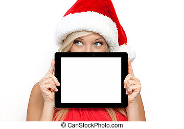 blonde girl in a red Christmas hat on New Year, holding tablet computer touch pad gadget with isolated screen