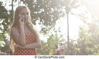 blonde girl in a red polka-dot dress standing poses