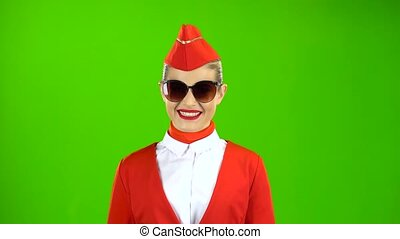 Blonde girl in a red suit is walking in sunglasses. Green Screen