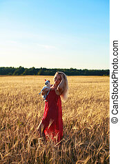 blonde girl in a wheat field at sunset holding a dog in her arms