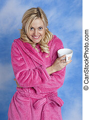 Girl wearing pink bathrobe in front of blue sky holding coffee cup