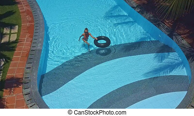 blonde girl in bikini goes out of pool with ring -...