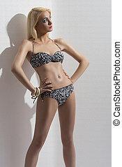 blonde girl in bikini near the wall looks at left