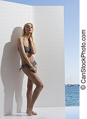 blonde girl in bikini near the wall with hand near the neck