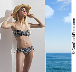 blonde girl in bikini near the wall with hat