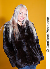 blonde girl in black coat on a yellow