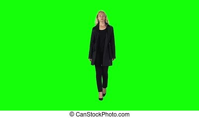 Blonde girl in black coat, trousers and high-heeled shoes ...