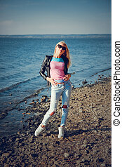 Blonde girl in black glasses and jeans posing on the beach...