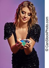 Blonde girl in black sequin dress is showing handful of multicolored chips, posing on colorful studio background. Gambling, poker, casino. Close-up.