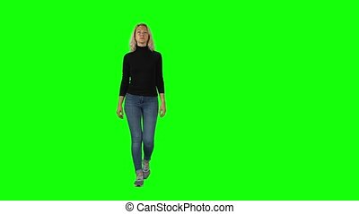 Blonde girl in black turtleneck, jeans and sneakers going ...