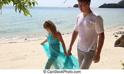 blonde girl in blue dress and  boyfriend walk along  beach