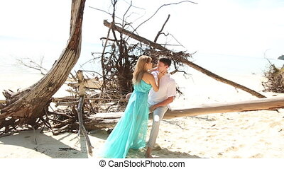 blonde girl in blue dress kisses with passion guy sitting on log among dry trees