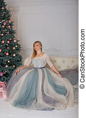 Blonde girl in evening dress sitting on a sofa