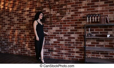 Blonde girl in evening dress with a neckline near brick wall. Slow motion .