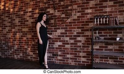 Blonde girl in evening dress with a neckline near brick...