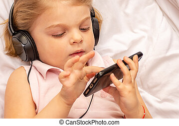 Blonde girl in headphones plays, listens to music on the phone.