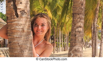 blonde girl in lace closeup looks out of palm trunk on beach