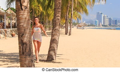 blonde girl in lace runs to palm arms trunk on beach