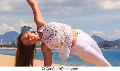 blonde girl in lace shows yoga asana half moon on beach