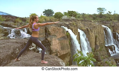 blonde girl in pink top stands on stone by waterfall