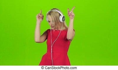 Blonde girl in red dress dancing in headphones, green screen...