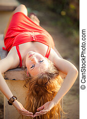 blonde girl in red dress lay on the bench