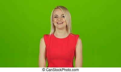 Blonde girl in red dress sincerely, contagious laughs. Green screen
