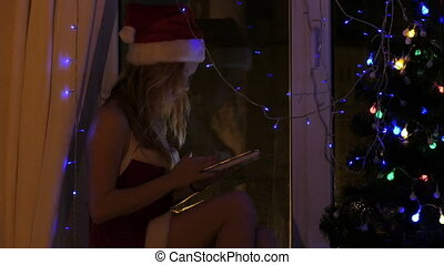 Blonde girl in santa hat with a tablet