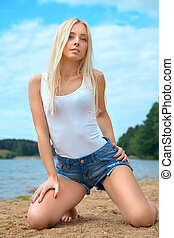blonde girl in shorts and t-shirt sitting at the water