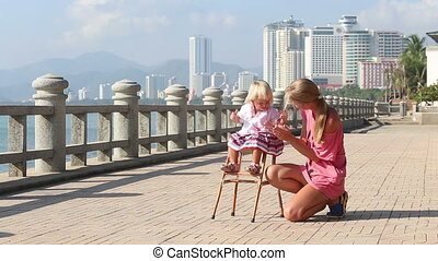 blonde girl in sits on chair and mother claps