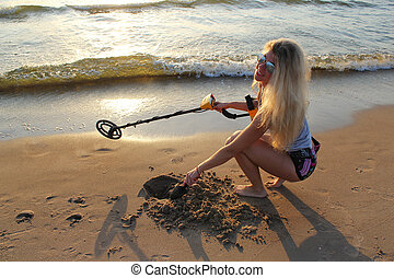 blonde girl in sunglasses with metal detector on the beach.