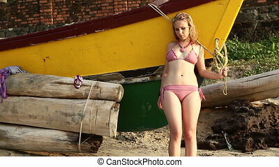 blonde girl in swimsuit  poses near boat