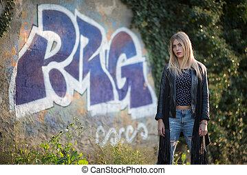 Blonde girl in the street in front of murals
