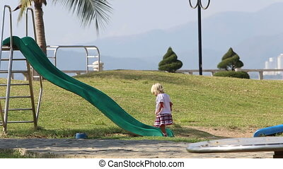 blonde girl in Ukrainian blouse comes to slide to climb