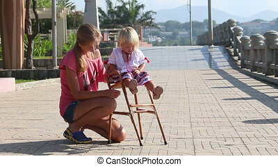 blonde girl in Ukrainian blouse sits on child's chair outdoor