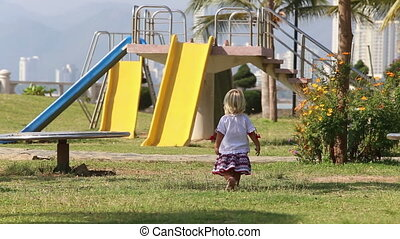 blonde girl in Ukrainian blouse walks to slide on play ground