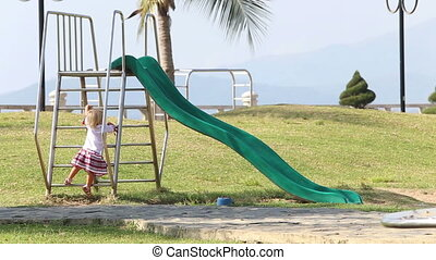blonde girl in Ukrainian climbs up on slide falls but holds out