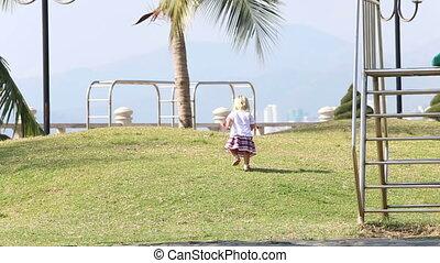 blonde girl in Ukrainian runs up hill on playground under palm