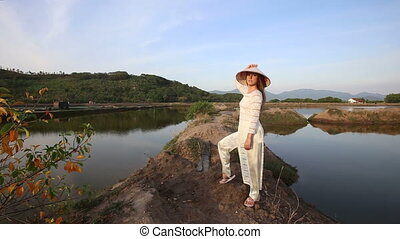 blonde girl in vietnamese costume and hat poses between ponds